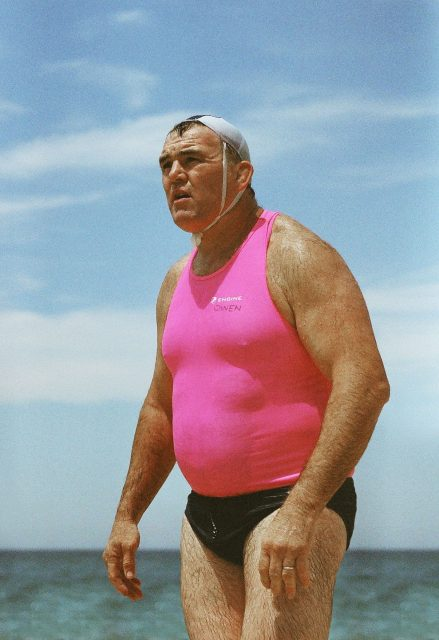 A large man in a tight pink swim top, small swimming trunks and tiny swim cap