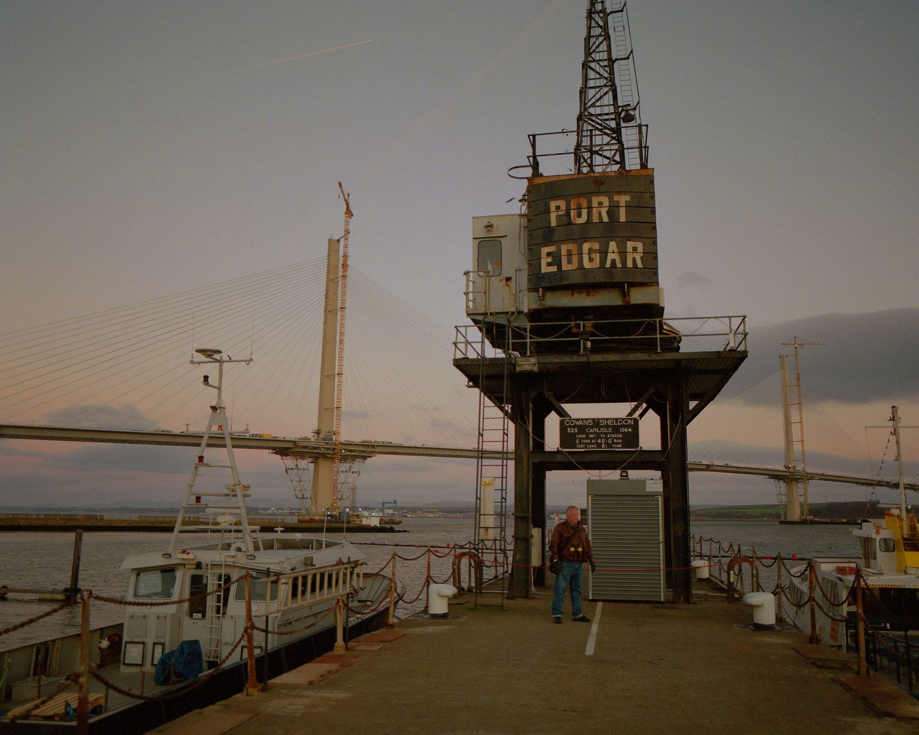 A man stands in front of a large boat crane at Port Edgar harbour during blue hour