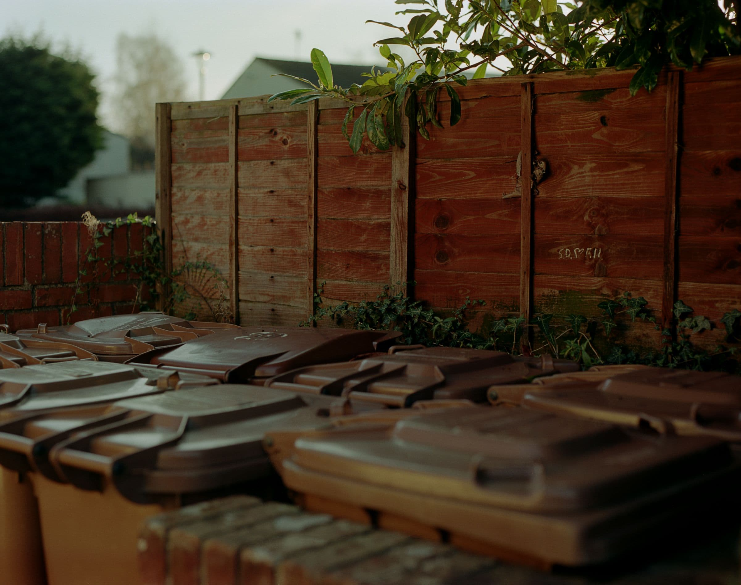 Brown wheelie bins tightly packed into a walled area in a suburban neighbourhood